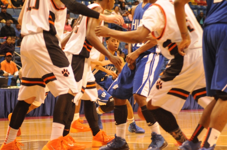 Basketball player eyes a spot to dribble to as others scurry about.